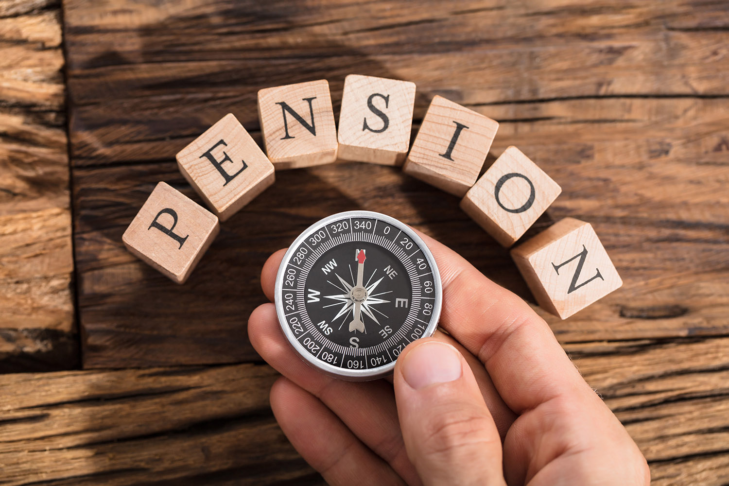 Compass and building blocks that spell out pension