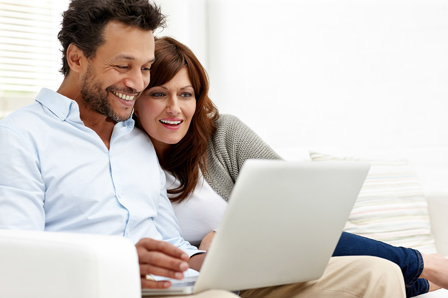 Happy couple together on couch with laptop
